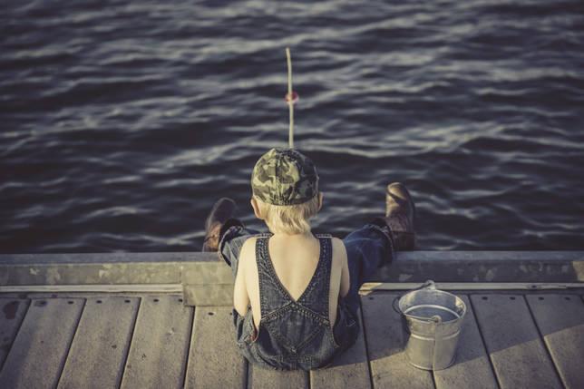 Маленький рыболов с удочкой на мостике